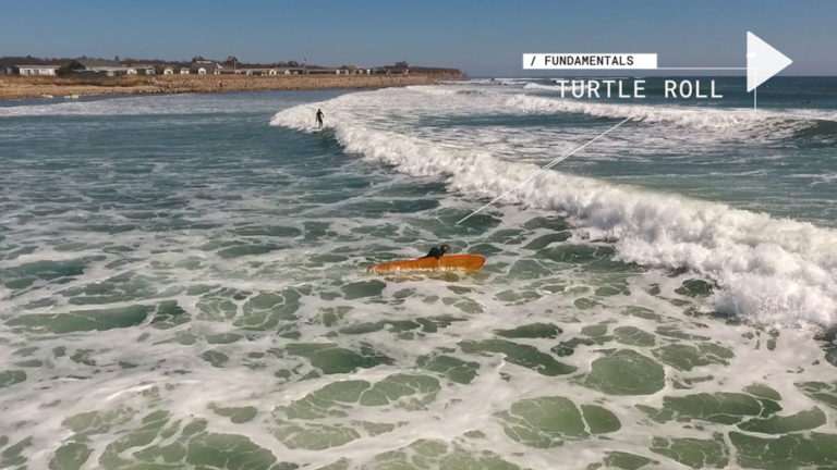 Surfer demonstrating how to turtle roll a surfboard.