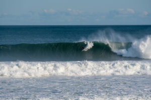 Coach Chris on one of the bigger set waves from hurricane larry